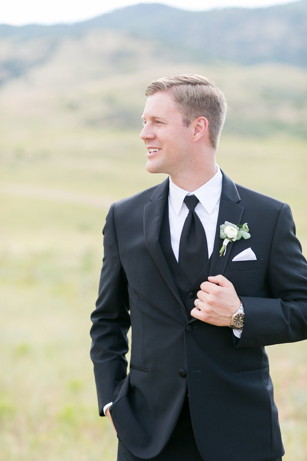 Groom standing in front of mountains