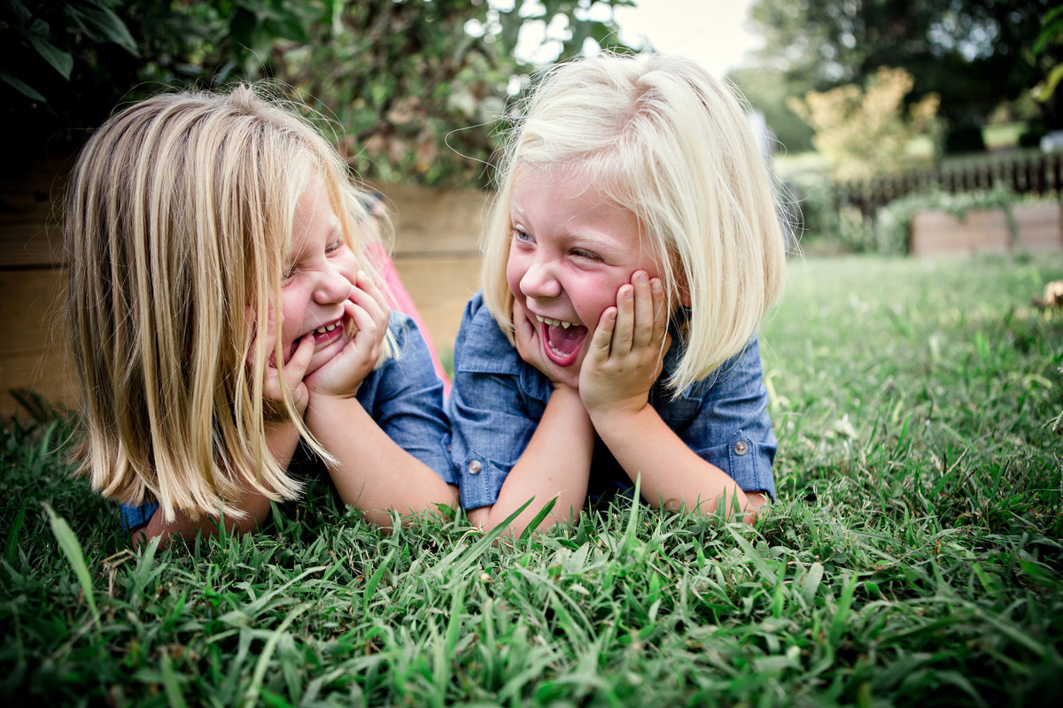 Twin girls making silly faces at each other laying on their stomachs in the grass for their family pictures by Knoxville Wedding Photographer, Amanda May Photos.