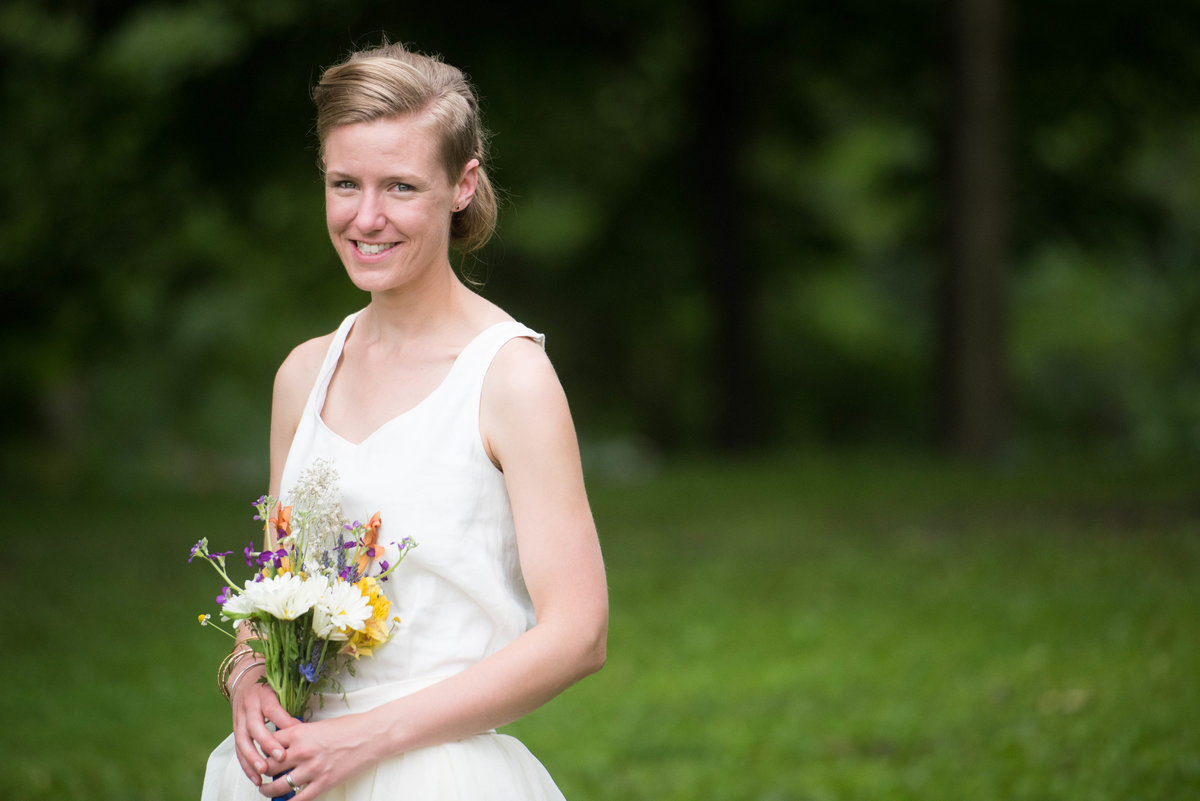Bride poses with bouquet by treeline, Chicago.
