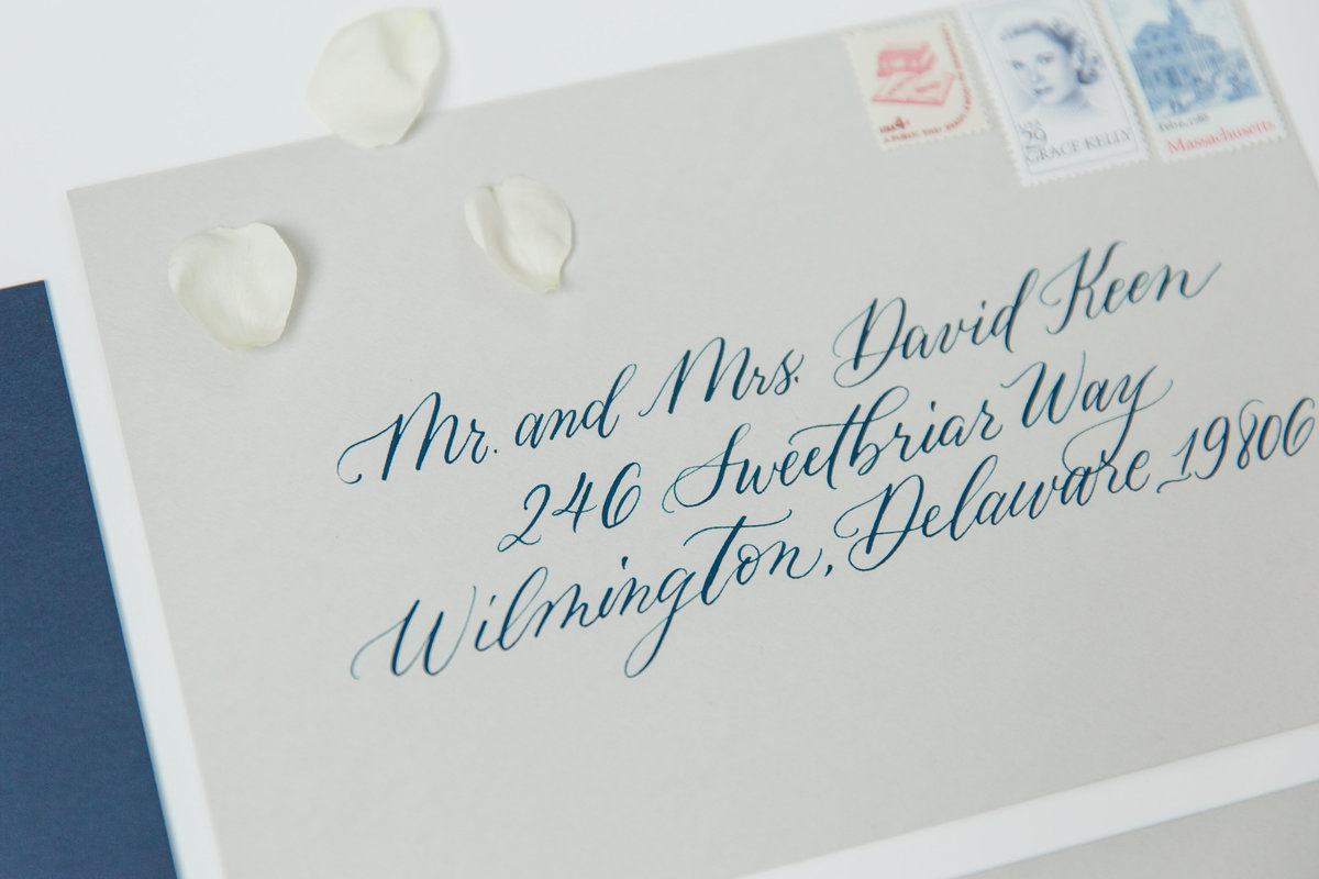 Gray envelope with calligraphy on navy blue ink
