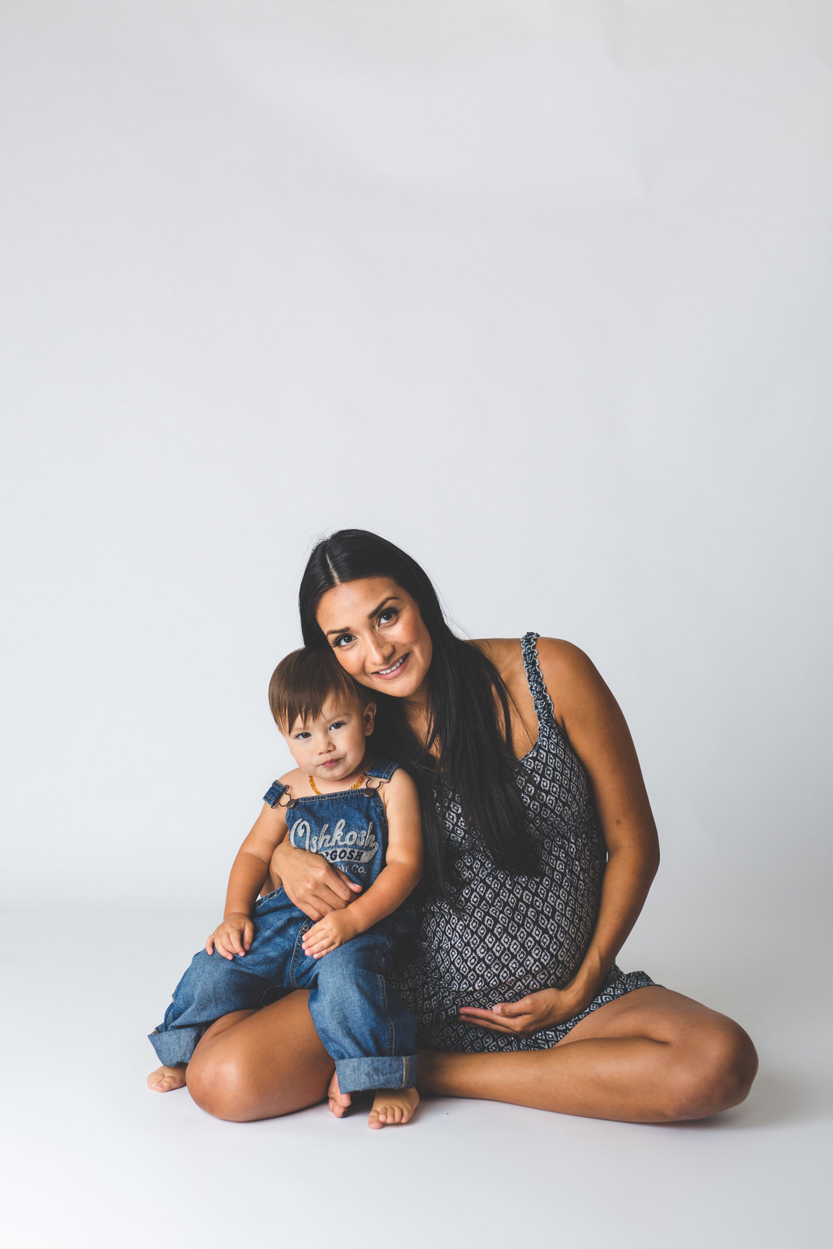 San Antonio In studio family maternity session on a white background with mother holding toddler son.