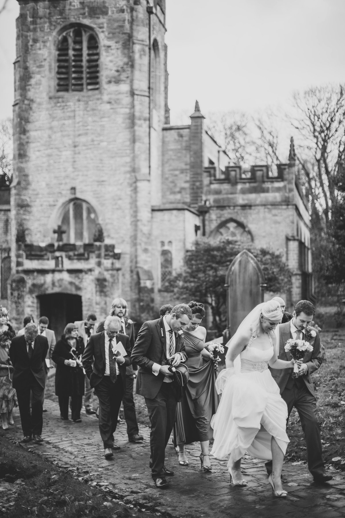 bride and groom walking out of church with friends behind