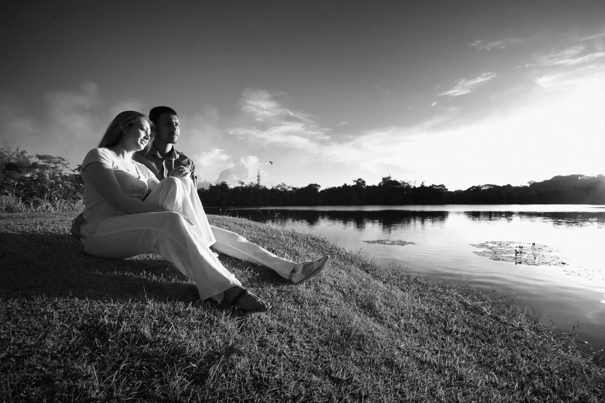 Couple sits on the bank or a lake during the sunset in a B+W capture. Photo by Ross Photography, Trinidad, W.I..