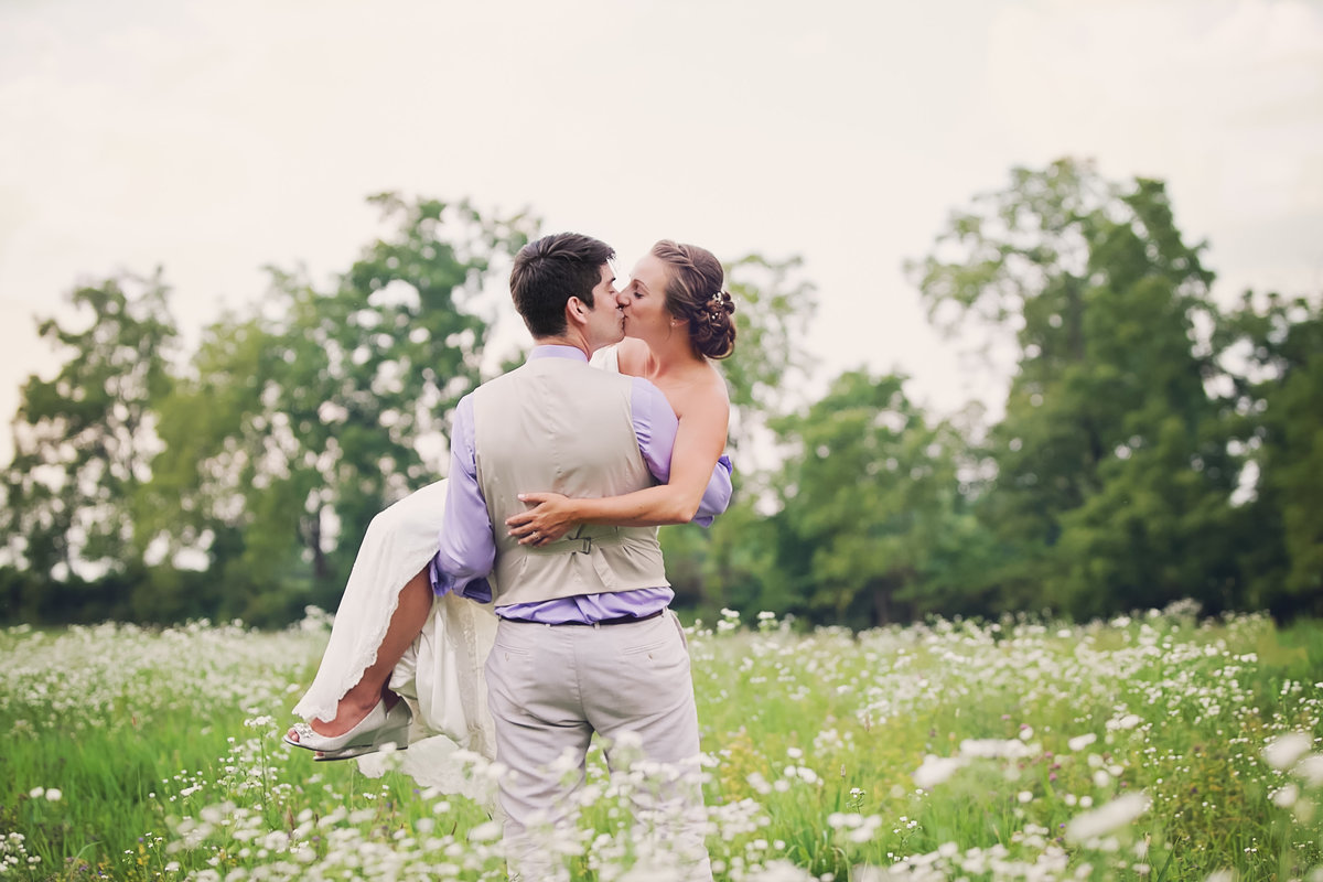 bride and groom in field of wildflowers by jana scott photography