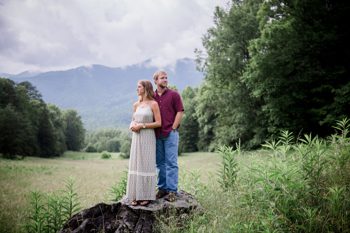 Standing on a rock in the middle of a field with Smoky Mountains behind them in Cades Cove engagement photo by Knoxville Wedding Photographer, Amanda May Photos.