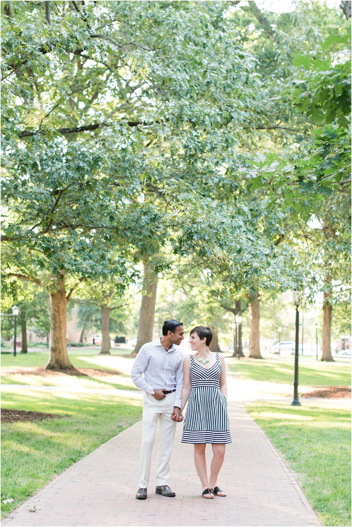 a bride wearing a black and white dress holding hands with her fiance looking at each other smiling on a brick walkway on UNC Chapel Hill campus
