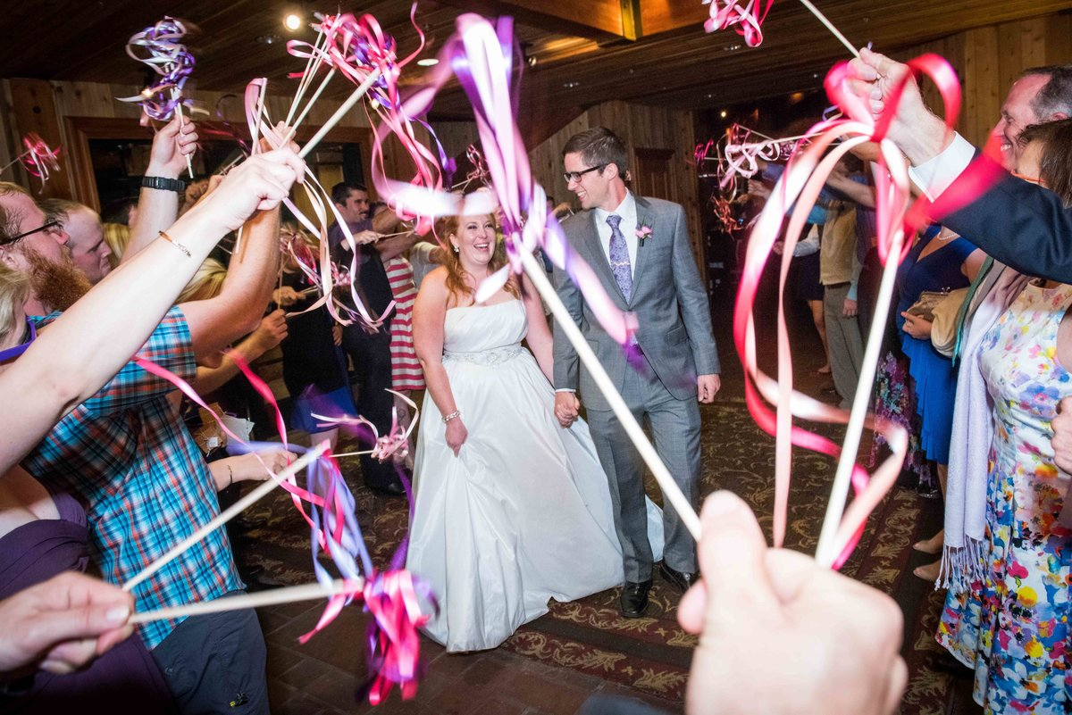 Bride and groom exit reception amidst streamers, Park City Utah.