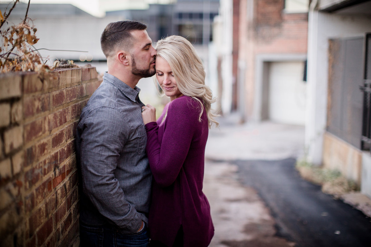 Leaning against brick wall in alley engagement photo by Knoxville Wedding Photographer, Amanda May Photos.