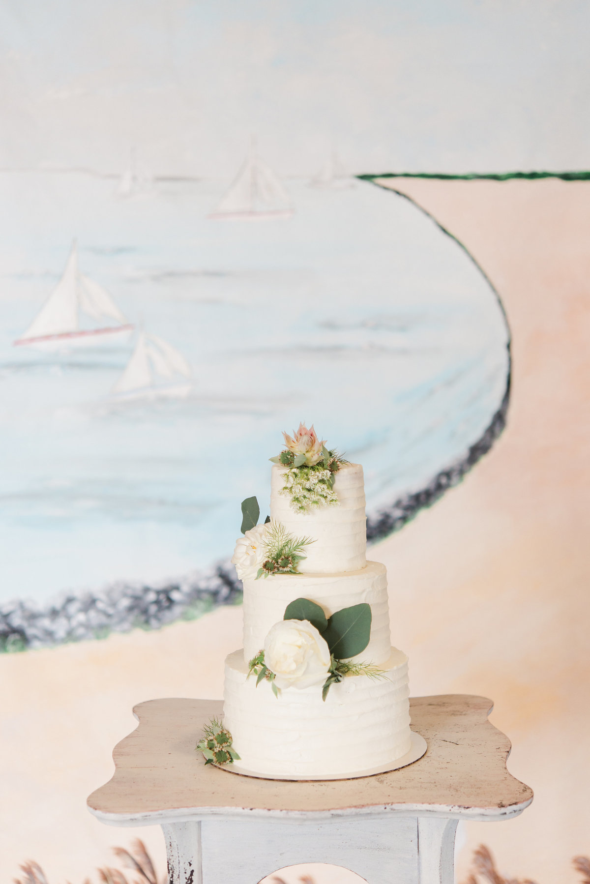 Cake in front of Chesapeake Bay inspired  wedding backdrop By Brittany Branson as featured in What's Up Wedding Magazine