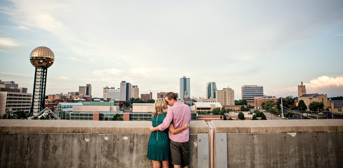 Engagement session of a couple standing in front of a cityscape view of Knoxville, TN by Knoxville Wedding Photographer, Amanda May Photos