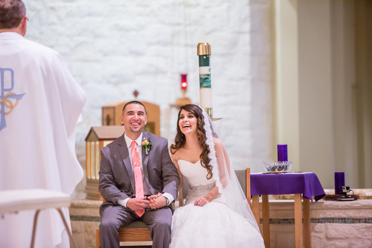 bride and groom laughing with priest during wedding ceremony at St. Dominics Catholic Church in San Antonio