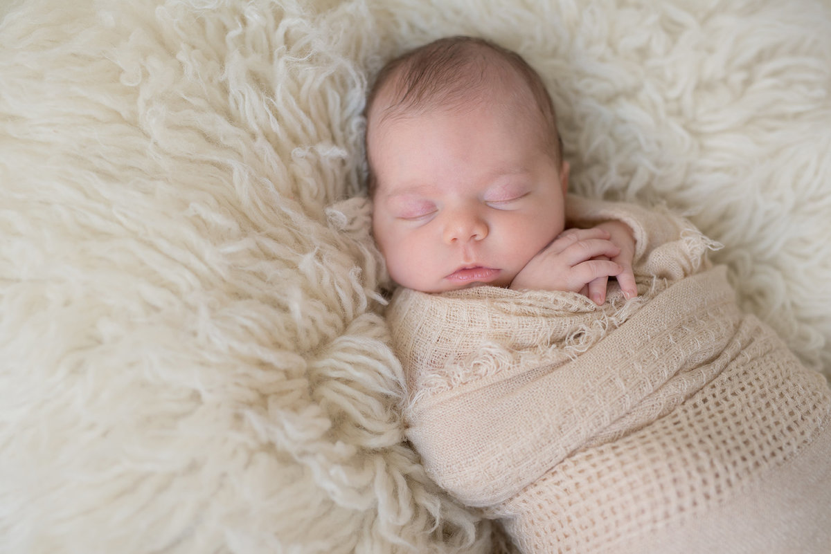 newborn baby girl wrapped in an ivory wrap sleeping
