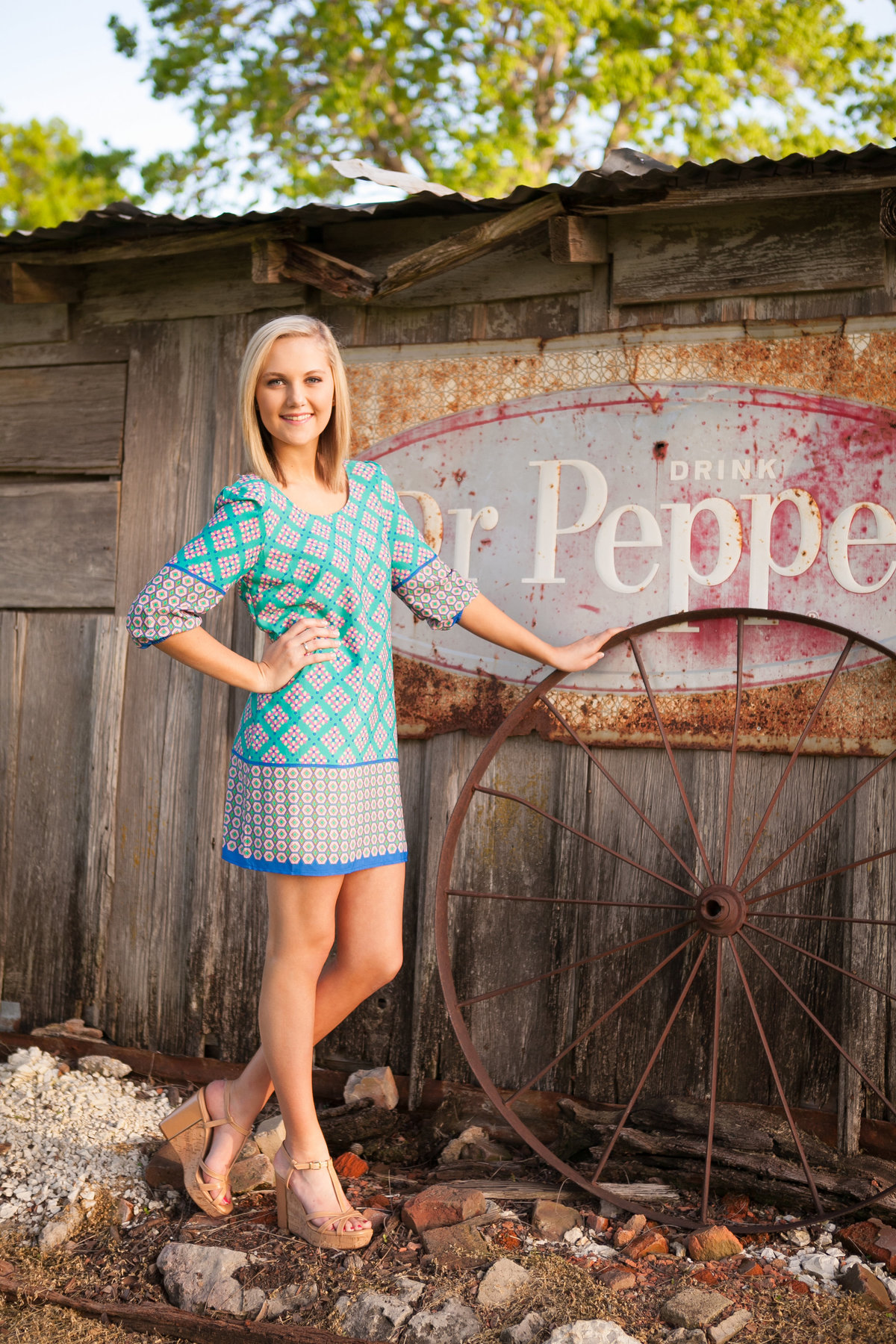 high school senior girl in front of barn with Dr. Pepper Sign in North Texas