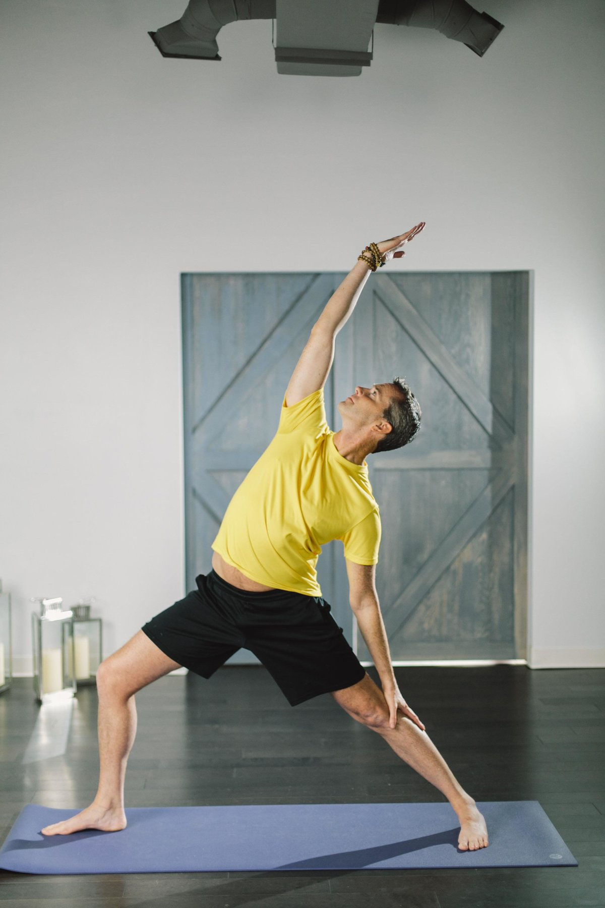Man does warrior pose in Kompose yoga studio