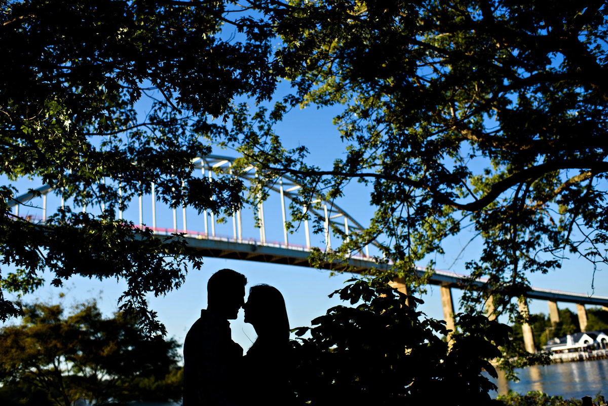 A silhouette of a couple under the Chesapeake bridge.