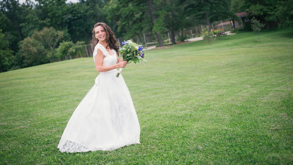 Bride smiles in open field with bouquet, Charlottesville VA.