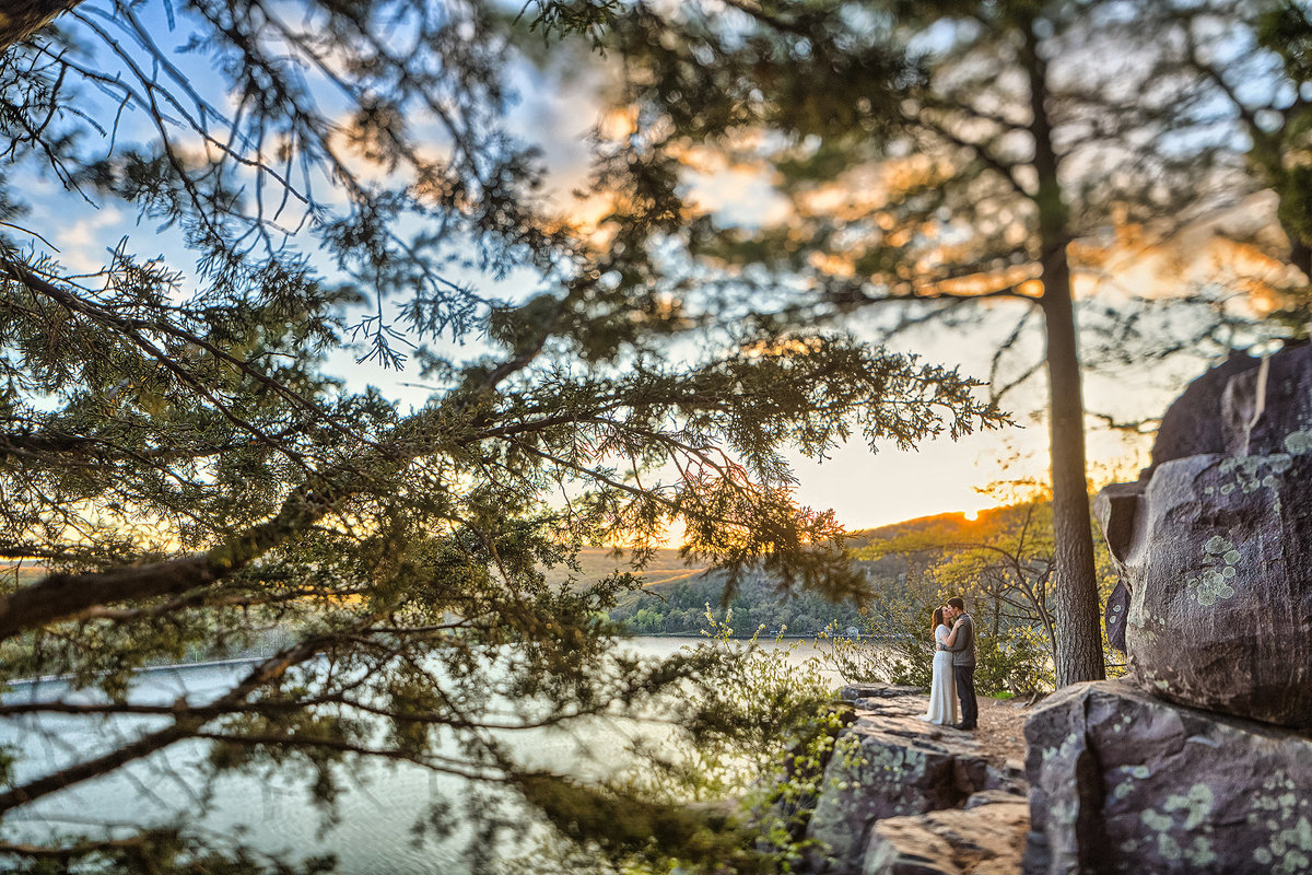couple kissing on a granite ledge at sunset in devils lake state park
