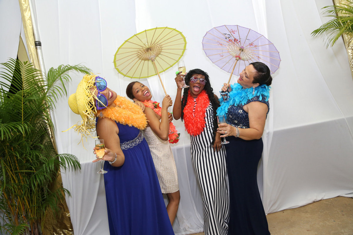 Four ladies enjoy a clean, white photobooth with boas, hats, and parasols. Photobooth by Ross Photography, Trinidad, W.I..