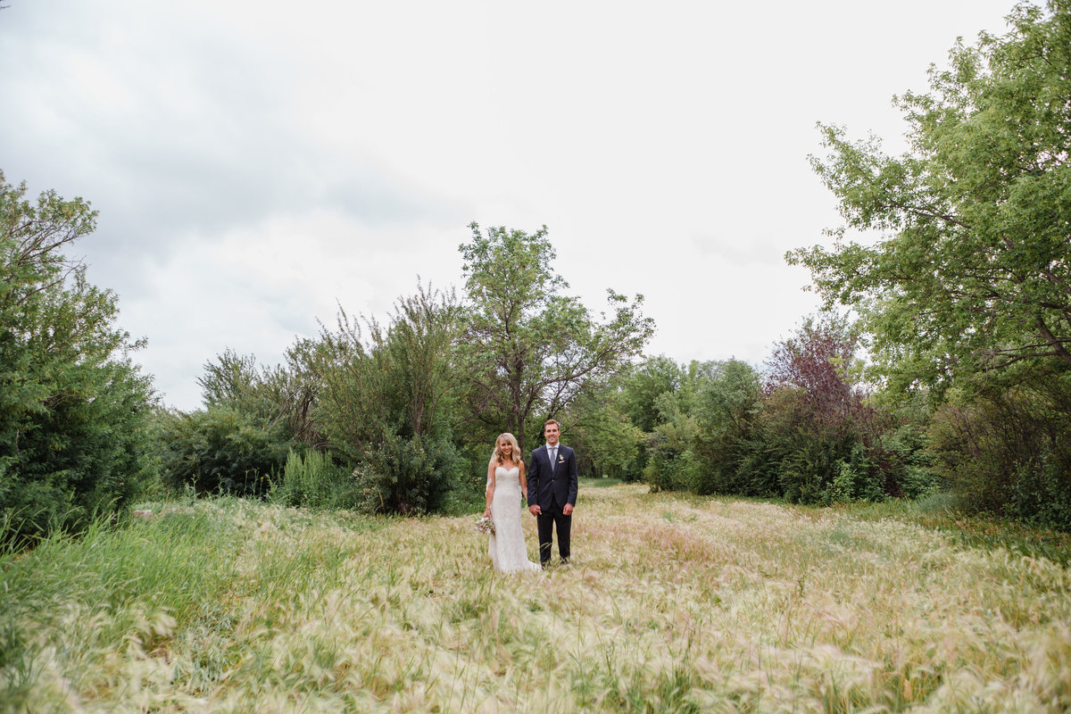 Modern couple stands in the wild grass in Wascana Park