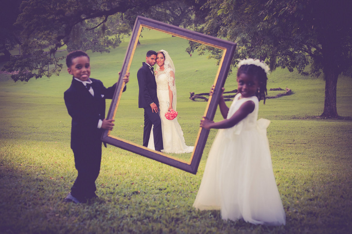 Bride and groom through picture frame held by ring bearer and flowergirl. Photo by Ross Photography, Trinidad, W.I..
