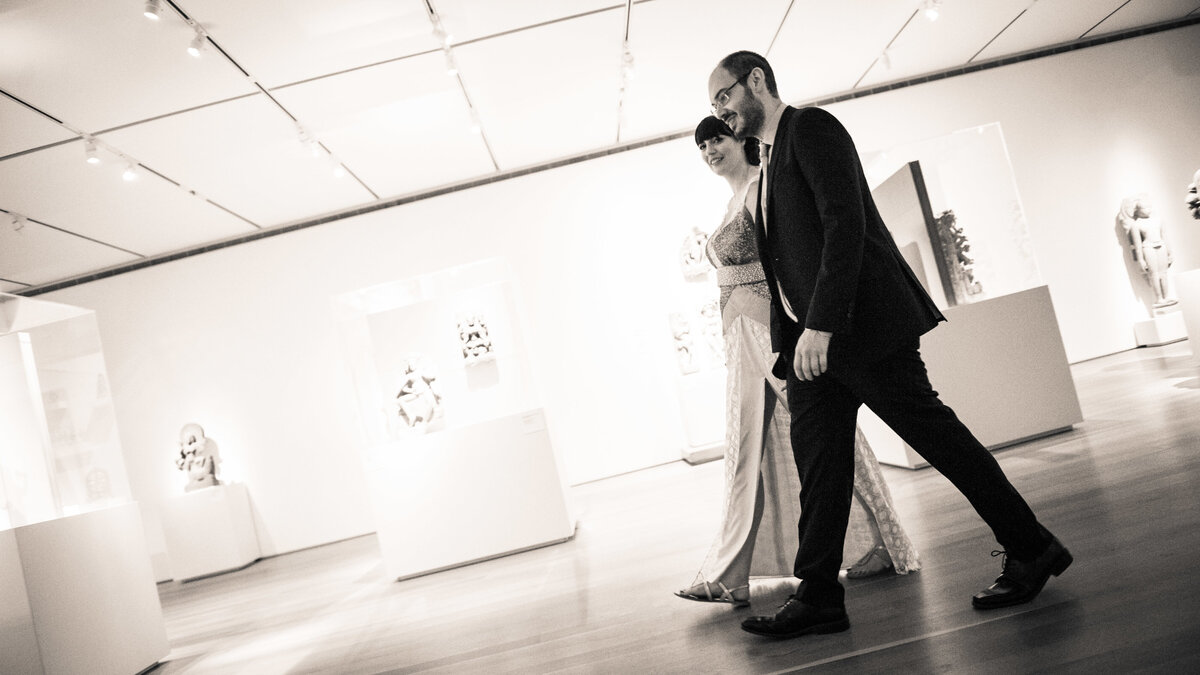 Couple, just married, walks through gallery art gallery at Art Institute of Chicago.