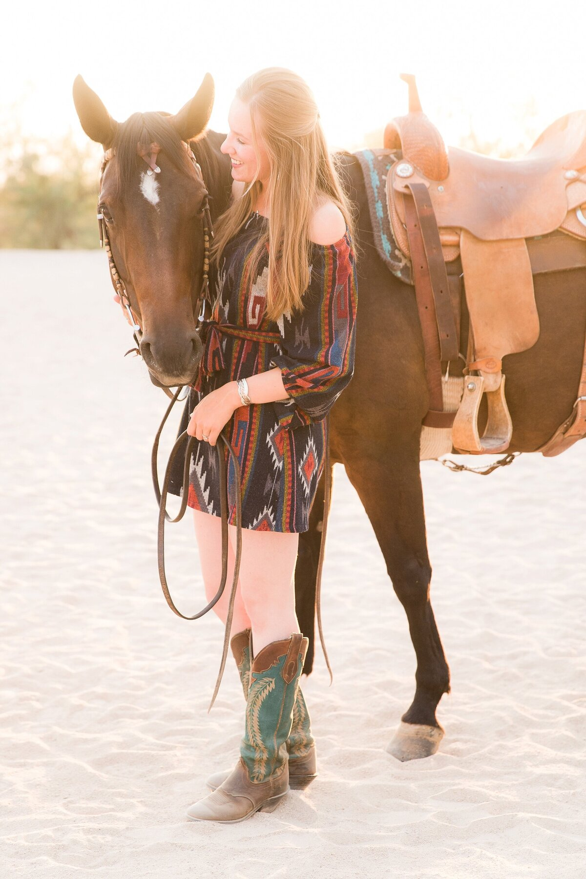 full length portrait of a girl standing next to her horse while the horse is looking at the camera and she's looking at the horse