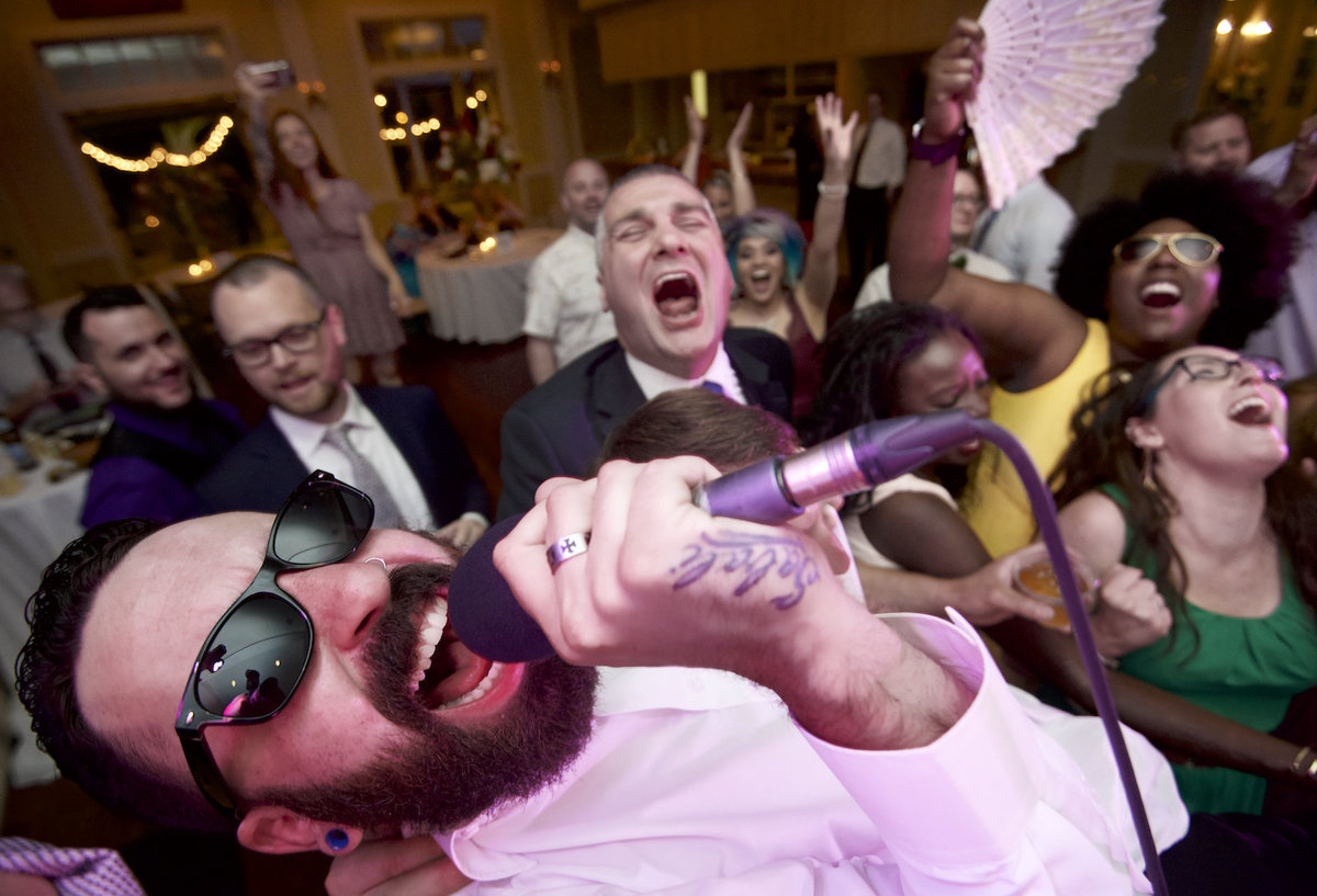 best man at wedding sings into microphone at New Orleans wedding