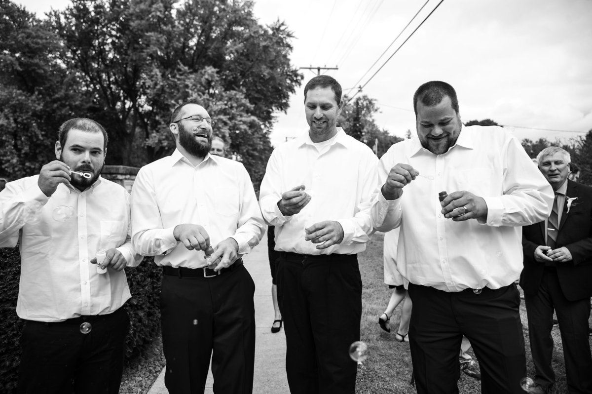 group shot of groomsman with bubble blowers