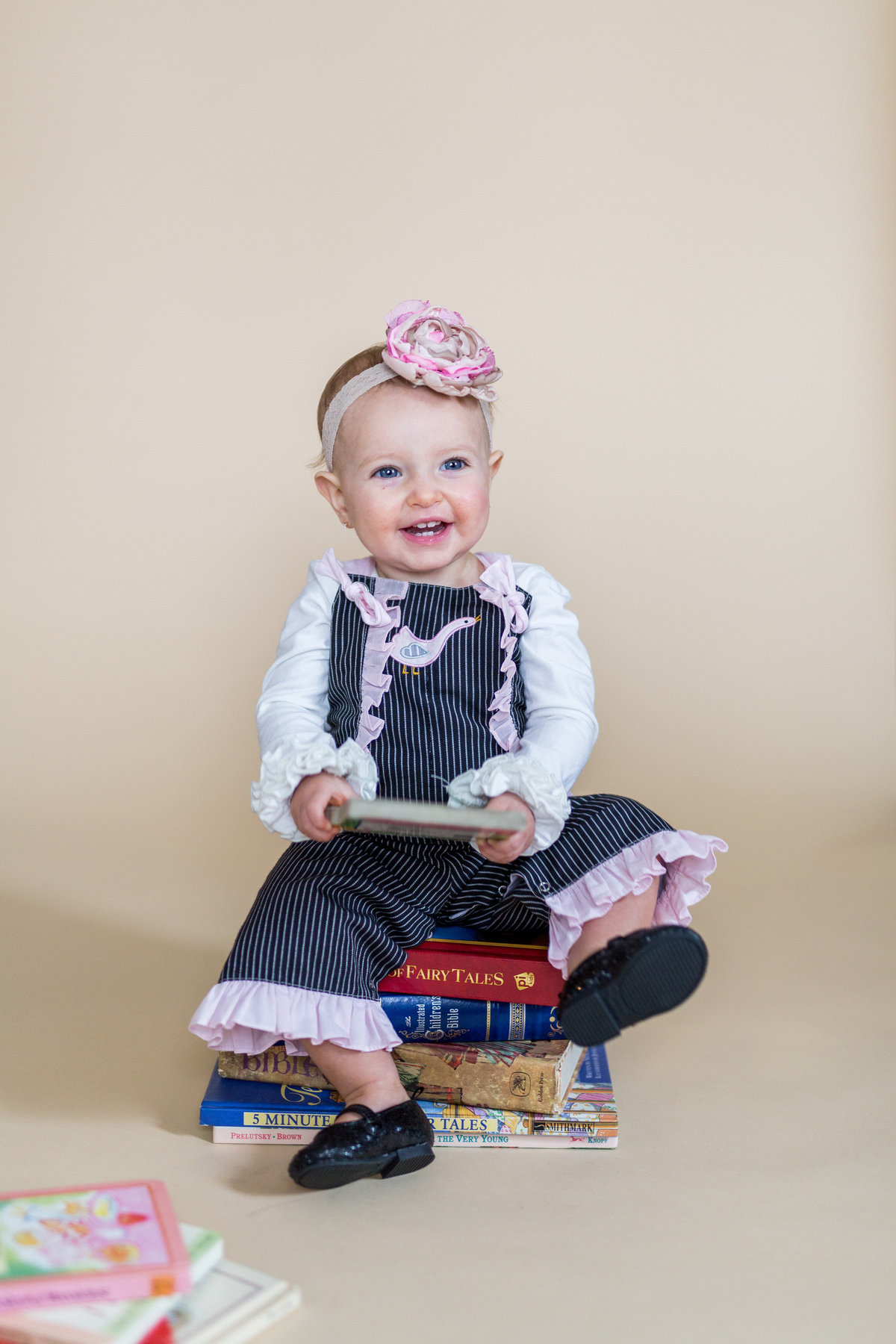 Baby's one year photography session of baby sitting on a pile of books and with a tan background in studio photo shoot.