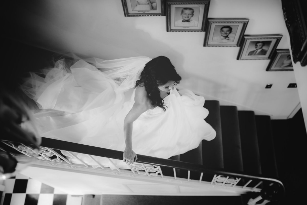 Bride walks down stairs at wedding venue in Live Oak, FL, Heritage Parks. Taken by documentary style wedding photographer