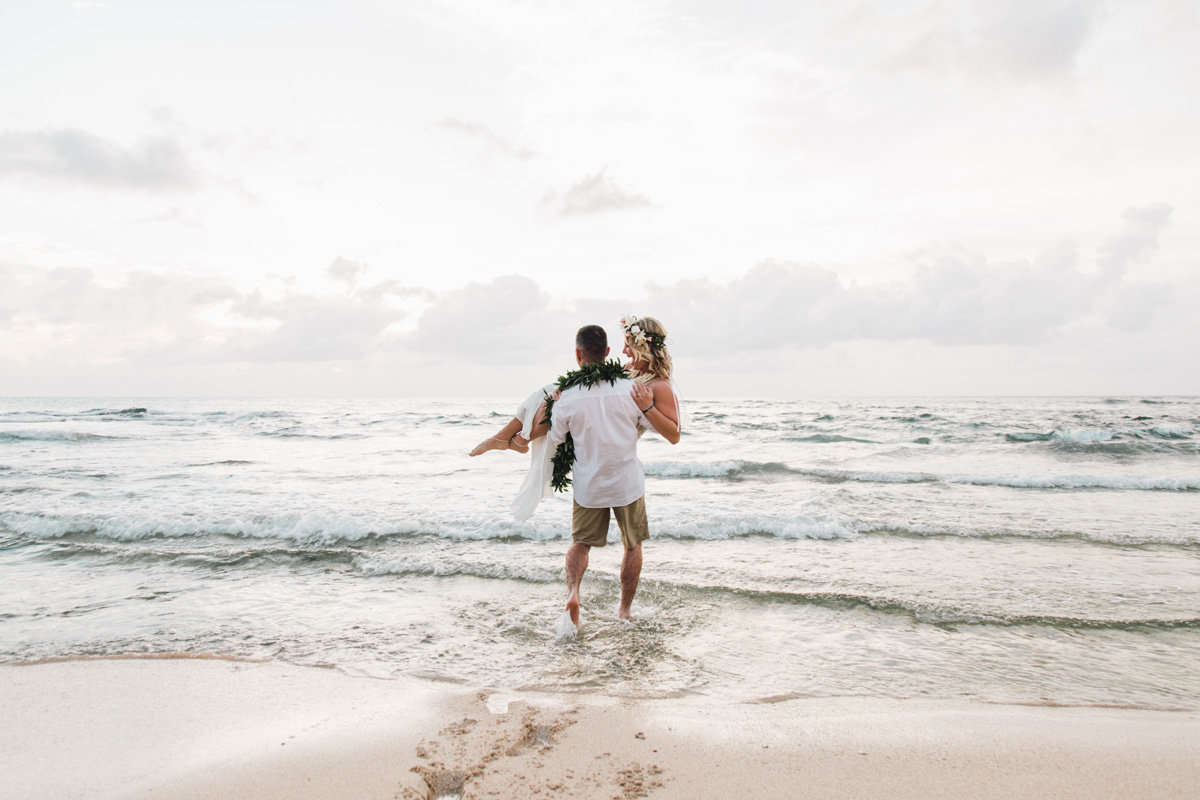 Groom carries bride into the ocean after they elope in Hawaii