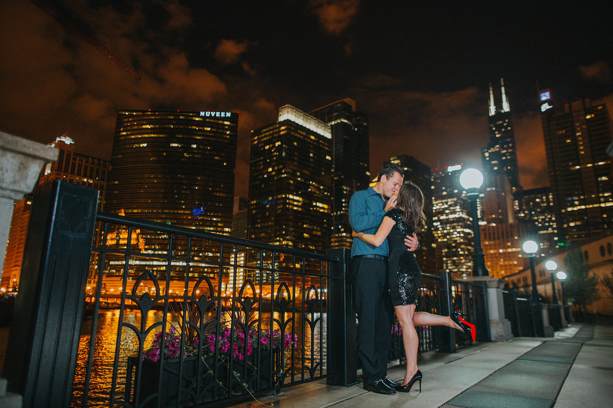 man and girl kissing during a nighttime engagement session in chicago illinois