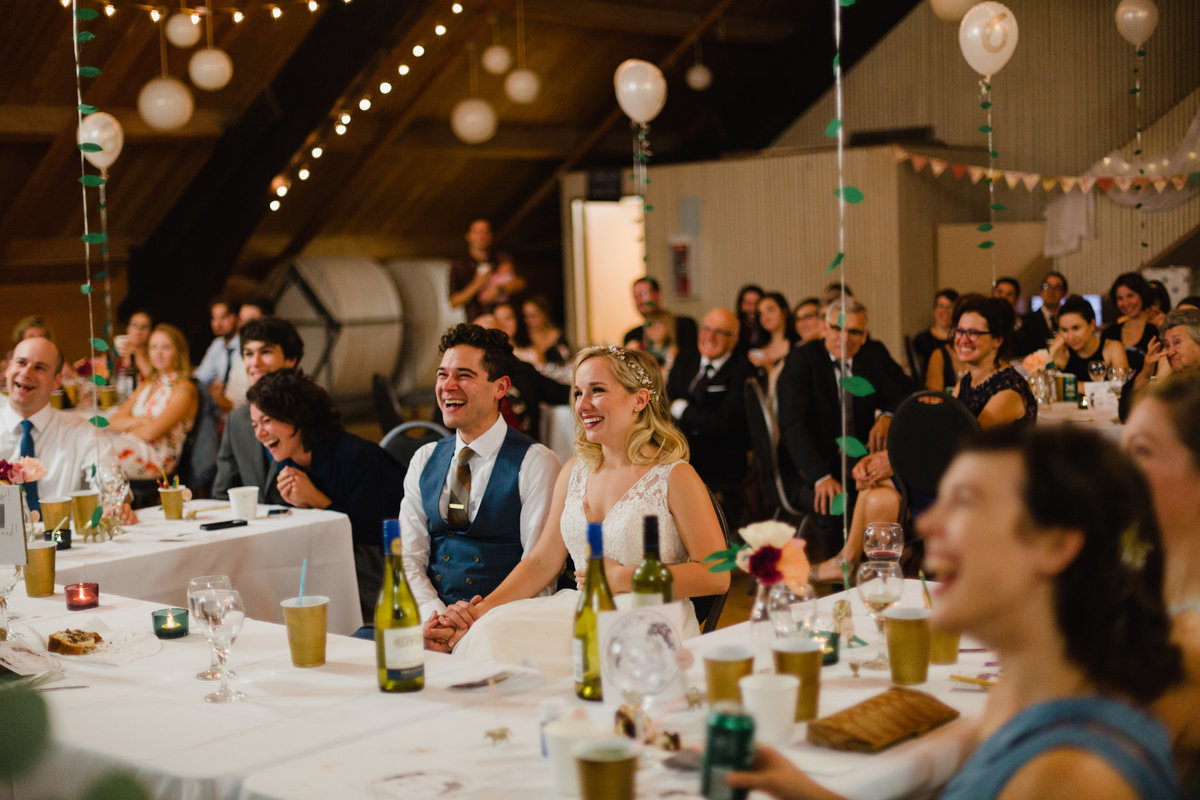 Couple laughing at their reception during speeches