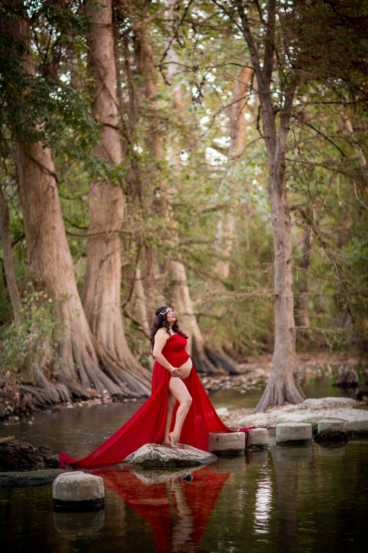 Maternity picture of pregnant woman in red dress holding baby belly and standing in a river.