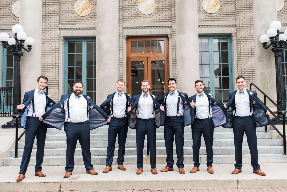 groomsmen showing off suspenders