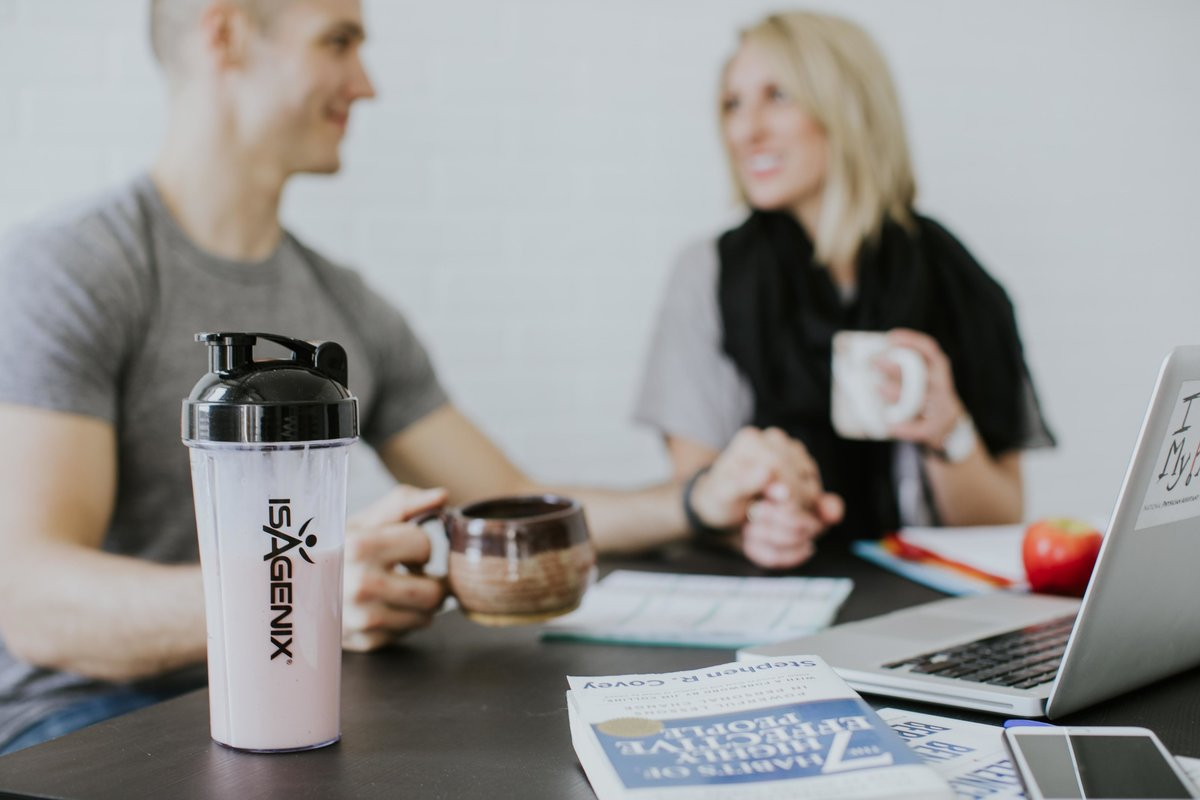 Couple sits hand in hand while working, drinking coffee behind a isagenix shake