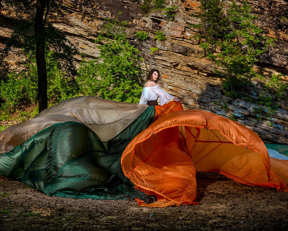 Creative photo shoot using parachute skirt by creek with cliffs.