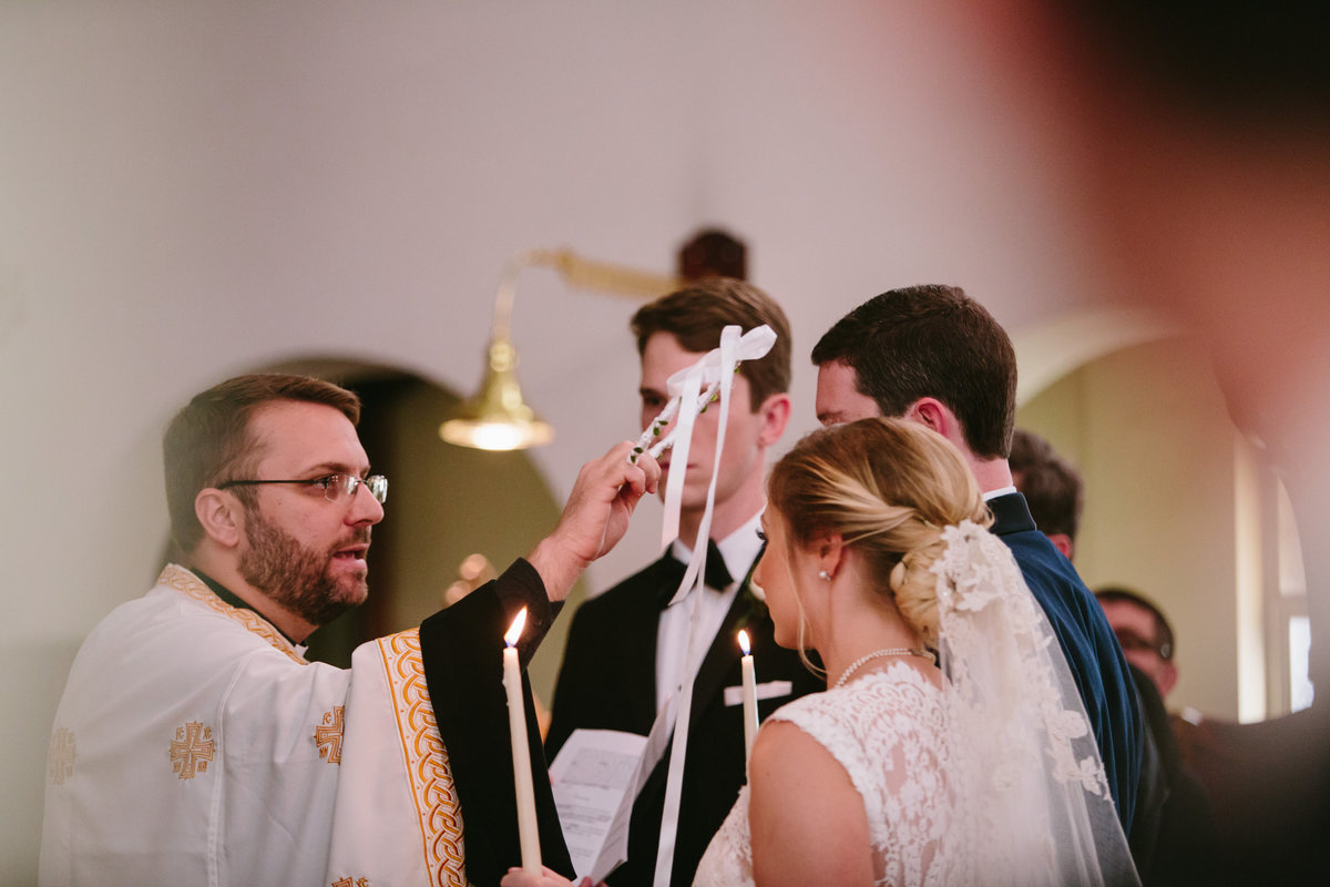 greek orthodox wedding ceremony preist putting crown on bride and groom