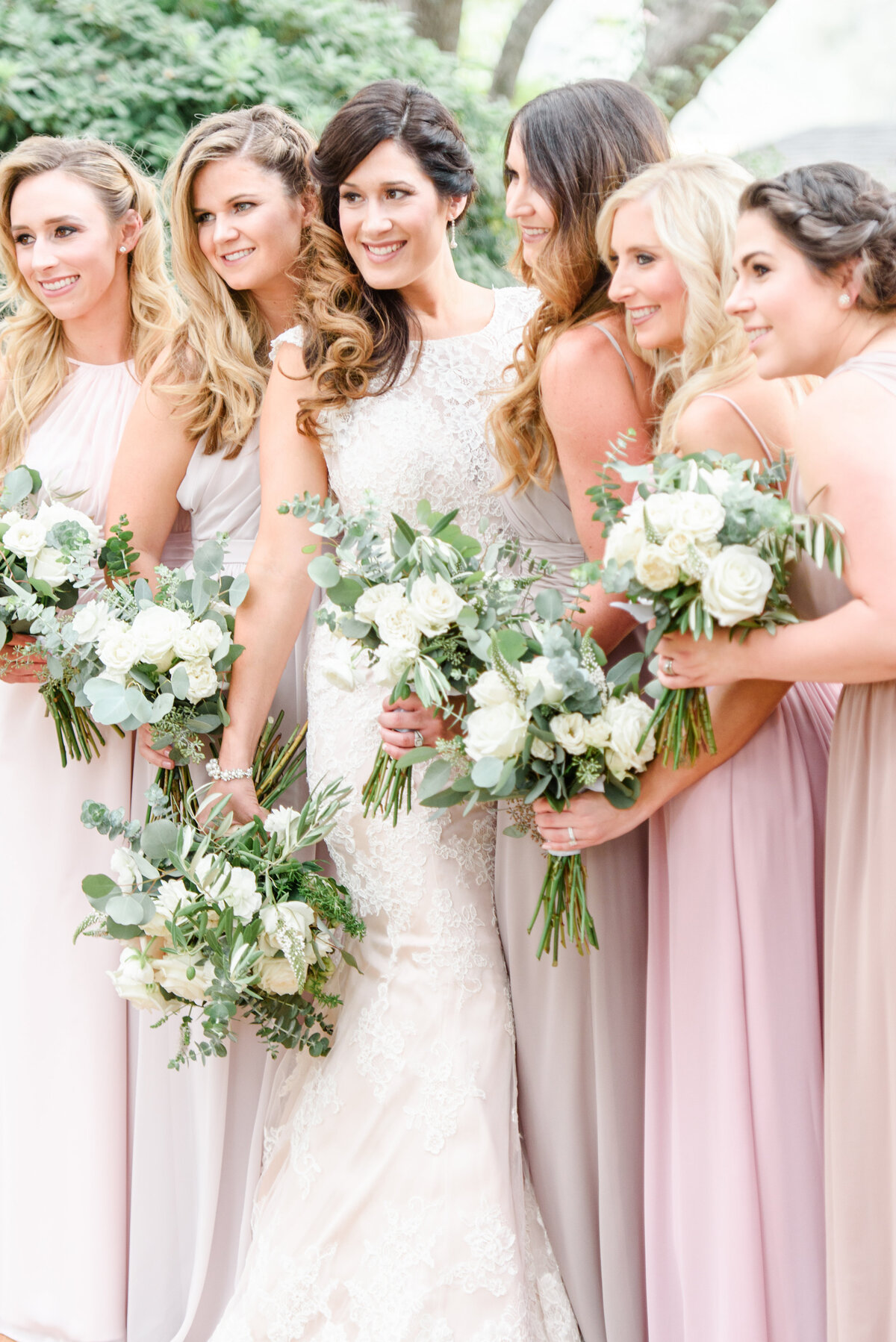 bride and her bridesmaids smiling with flowers