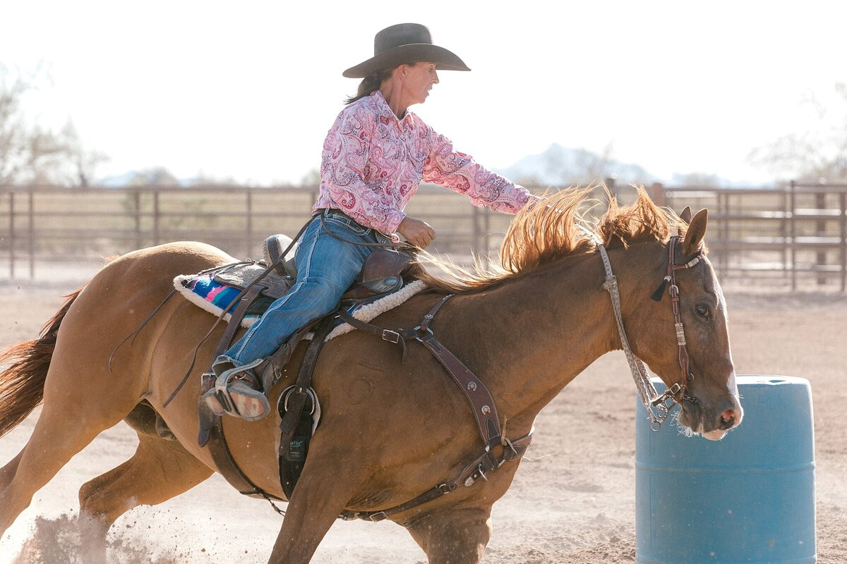 cowgirl racing around the barrel on her quarter horse
