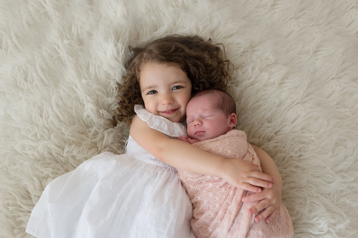 a toddler holds her new baby sister