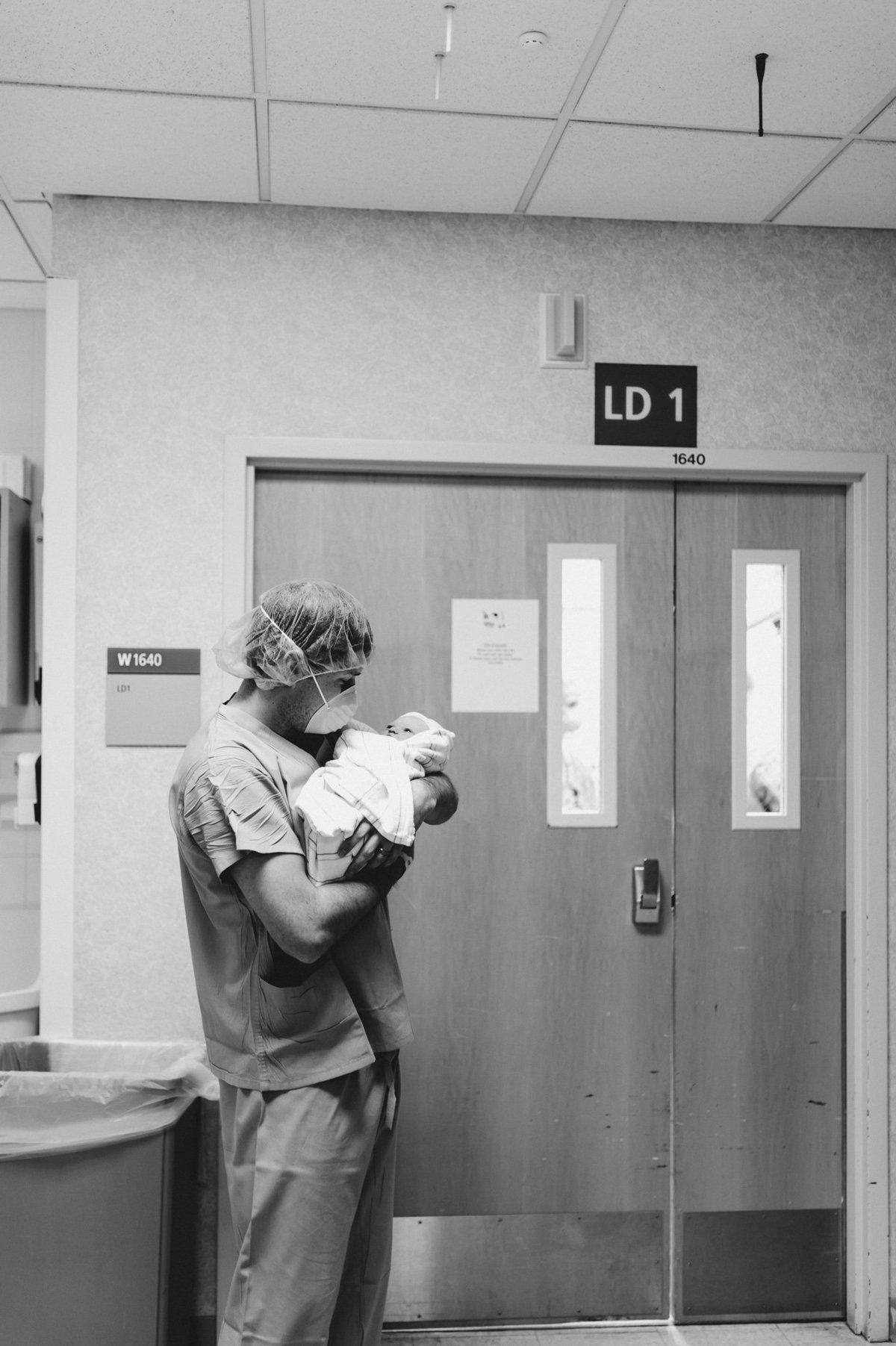 Dad standing outside of the OR holding his newborn daughter