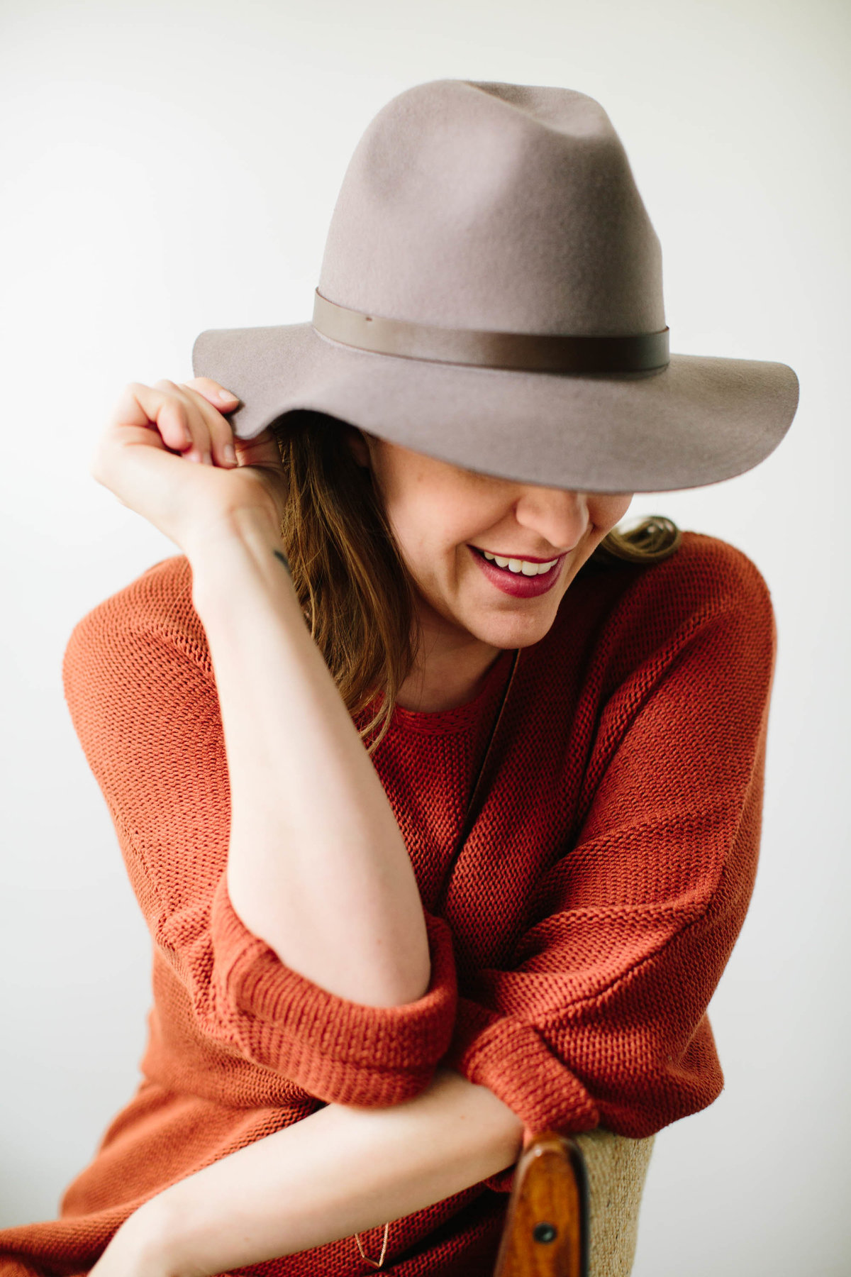 smiling woman with hat and orange sweater studio headshot