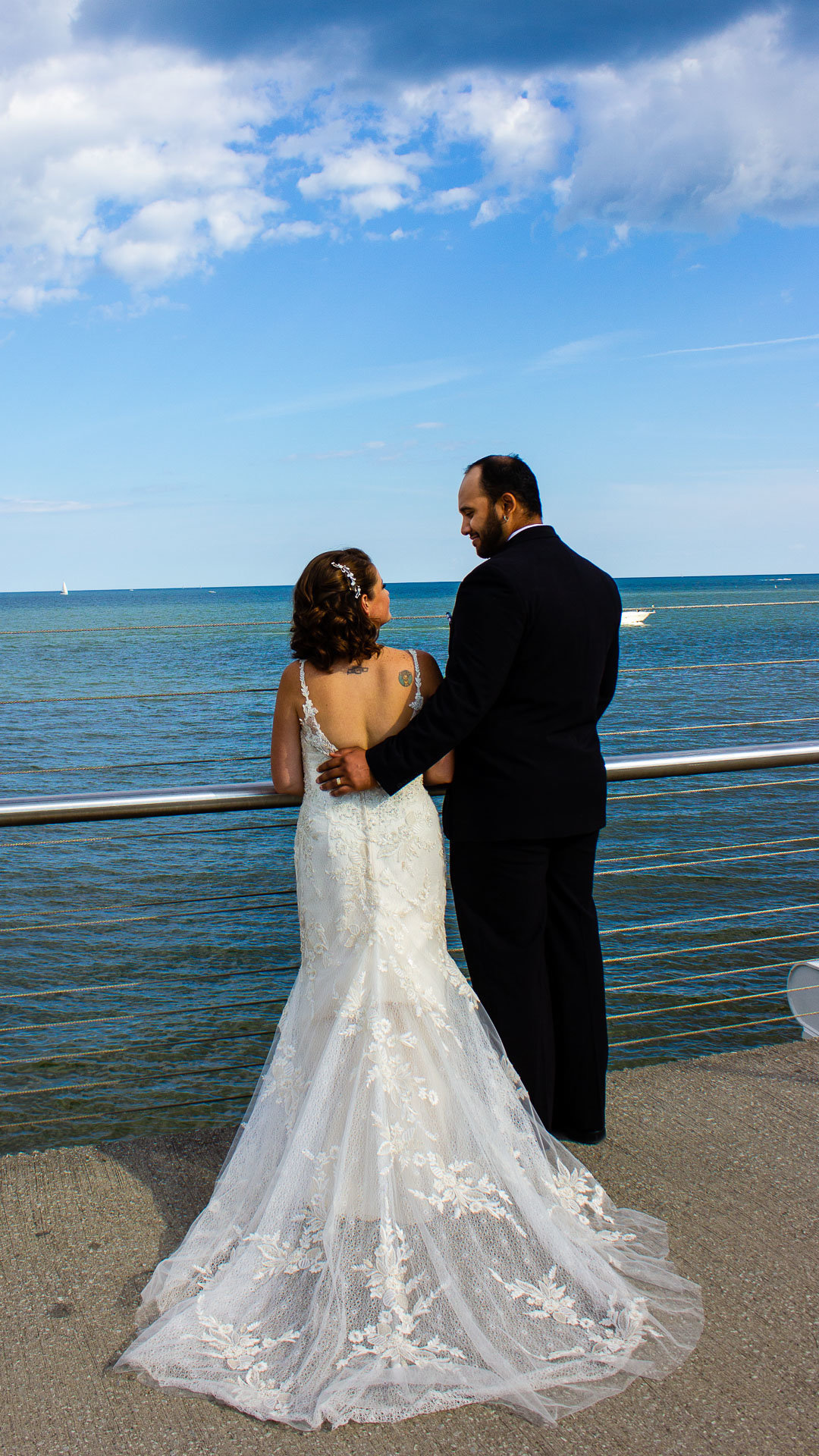 Bride and groom look at each other as they face a view of Lake Ontario from the bridge for their Wedding Portraits by Rosanna Radha Photography