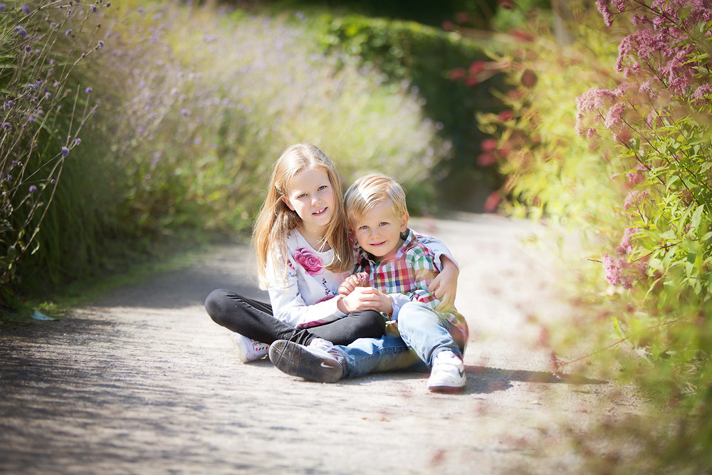 siblings sitting on path