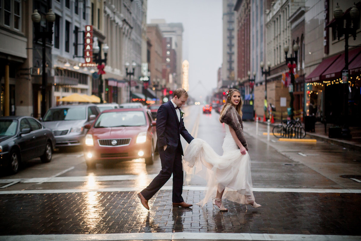 Bride and groom cross the street while groom carries bride's train at Jackson Terminal Wedding Venue by Knoxville Wedding Photographer, Amanda May Photos.