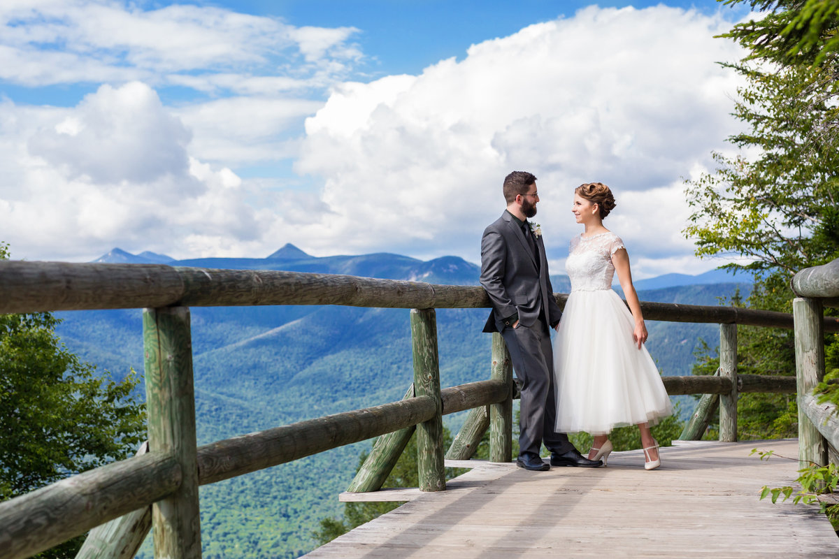 Loon Mountain Resort New Hampshire Wedding Photographer with the couple celebrating in front of the mountains in her tea length dress and classic hair style