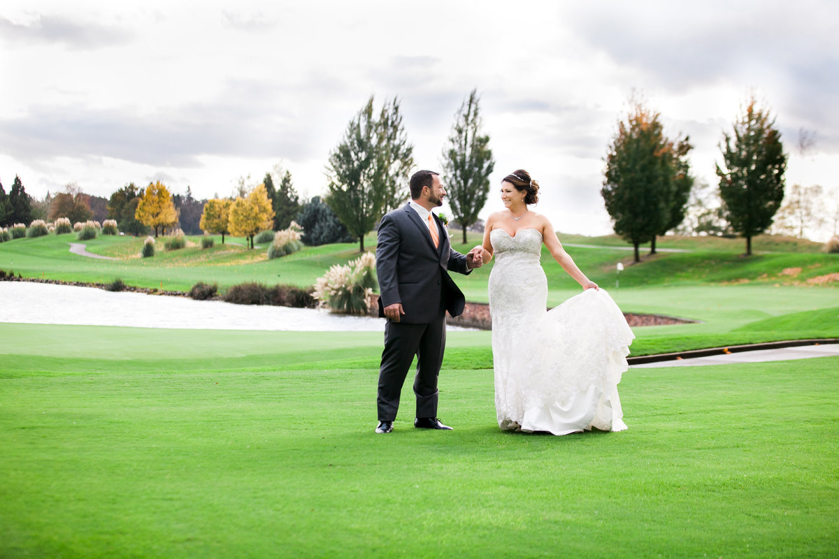 Oregon golf course wedding photo of bride and groom holding hands