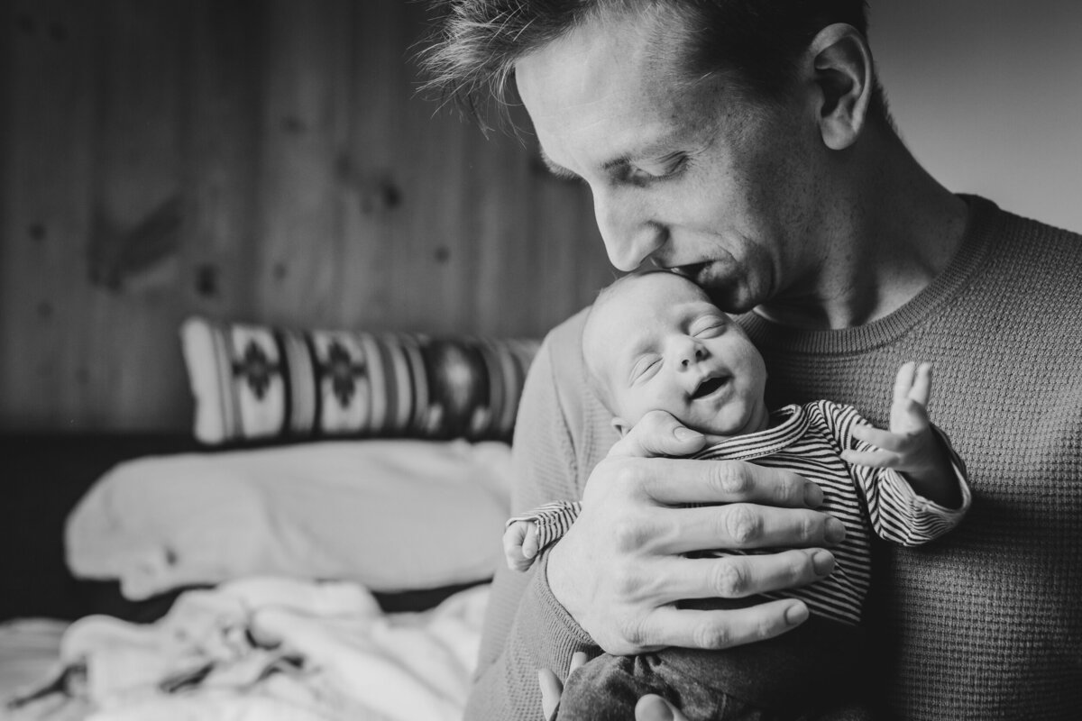 A three-week-old newborn smiles as her dad kisses the top of her head. This image is black and white.