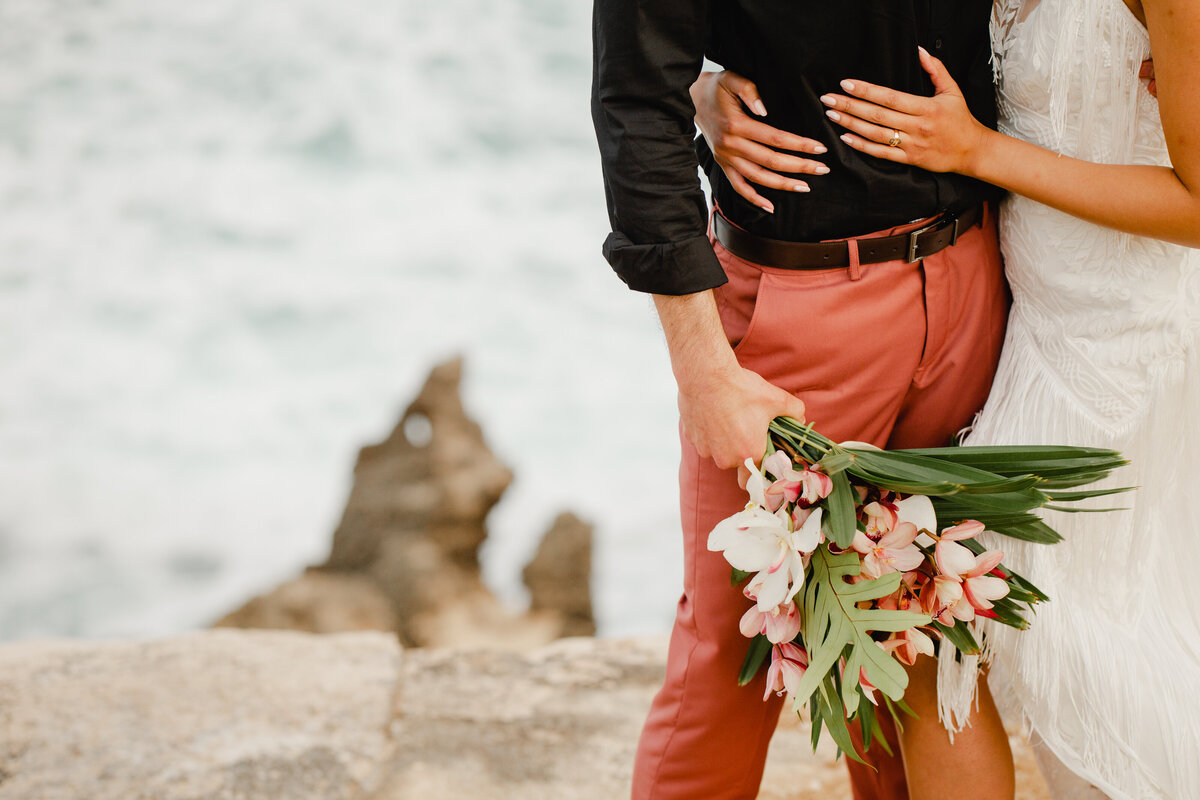 A detail photo of a bride with her arms around her groom's waist. He is holding her beautiful bouquet of flowers and they are standing on a beach in Hawaii.